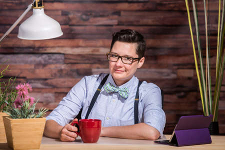 dapper: Smiling Dapper woman at stylish office desk with a red coffee mug