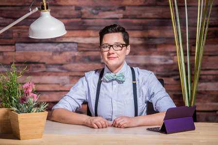 yuppie: Dapper bowtie wearing woman at stylish office desk with tablet
