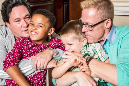 gay girl: Gay parents kissing and hugging their children Stock Photo