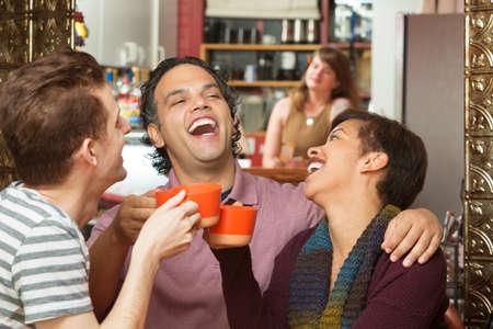 Happy group of three diverse adults laughing with coffee cups