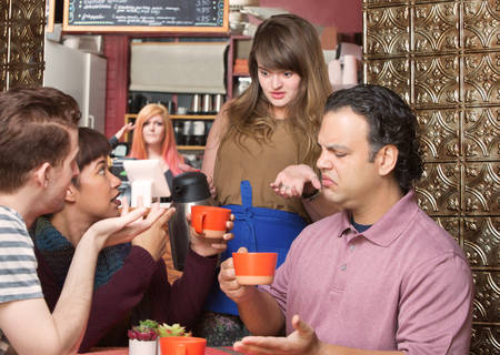Dissatisfied customers and waitress at coffee house Stock Photo