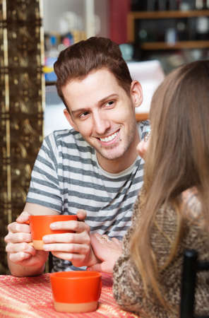 patron: Smiling young man with girlfriend in cafe Stock Photo