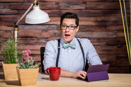 butch: Surprised dapper woman wearing glasses and bowtie using tablet computer