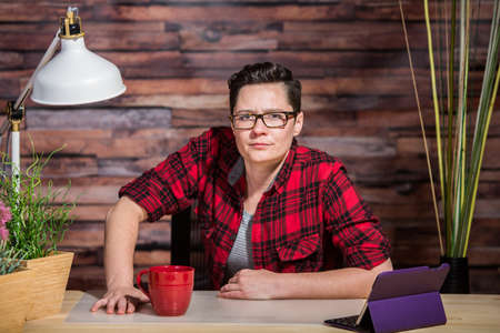butch: Woman in flannel shirt leaning on modern desk with red cup Stock Photo