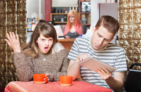 insulted: Insulted woman at table with young man using tablet Stock Photo