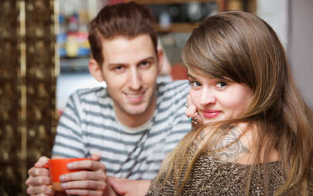 flattered: Handsome smiling man with cute woman in cafe