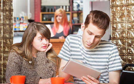 Sad woman looking over at boyfriend using computer tablet