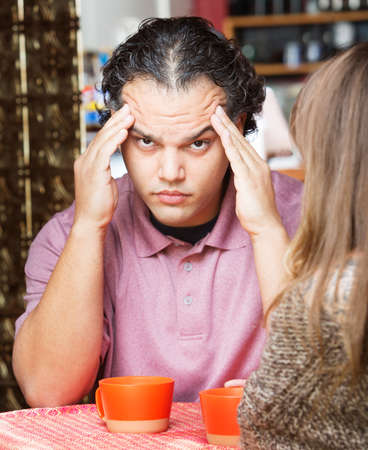 wrinkled brow: Stressed out man rubbing his head at table with friend Stock Photo