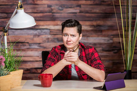 eyebrow raised: Woman wearing flannel shirt at desk with one eyebrow raised Stock Photo