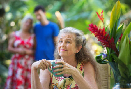 forgetful: Forgetful older mother with cup near couple Stock Photo