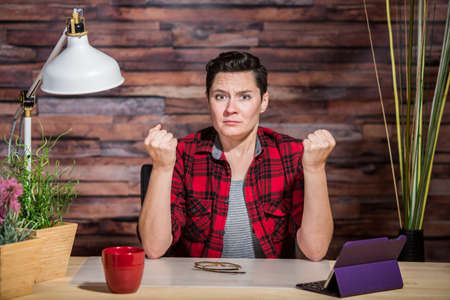 flannel: Frustrated woman in flannel shirt with clenched fists Stock Photo
