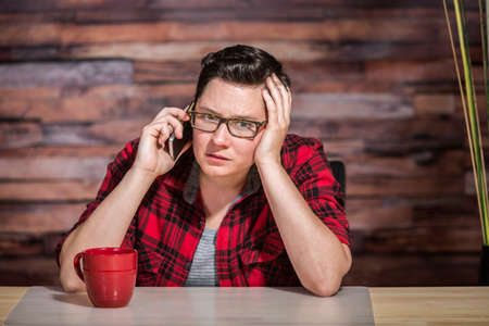 flannel: Serious woman wearing flannel shirt on smart phone in office Stock Photo