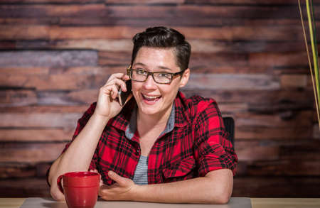 lesbian women: Enthusiastic woman in business casual outfit on phone
