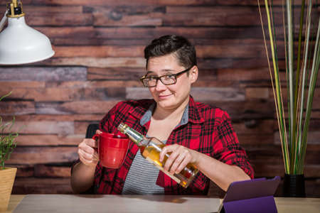 yuppie: Grinning woman pouring whiskey into coffee mug