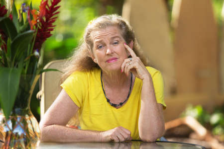 beautiful middle aged woman: Single mature woman in yellow with serious expression