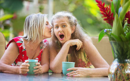 startled: Shocked mature woman listening to whispering friend