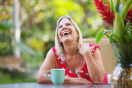 flattered: Attractive single mature woman at table laughing