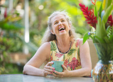 hysterical: Joyful senior aged woman with mug laughing outdoors