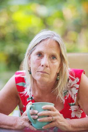 mujer triste: Simpático mediana edad de raza caucásica mujer que sostiene un café hasta Foto de archivo