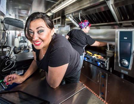 음식 트럭에 파란 눈을 가진 검은 머리 웃는 점원 스톡 콘텐츠