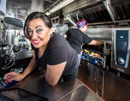 Dark haired smiling cashier with blue eyes on food truck