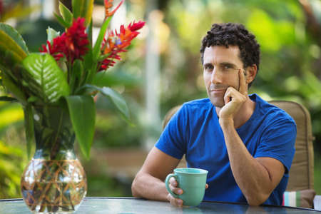 hand on the chin: Serious male adult sitting outdoors with hand on chin
