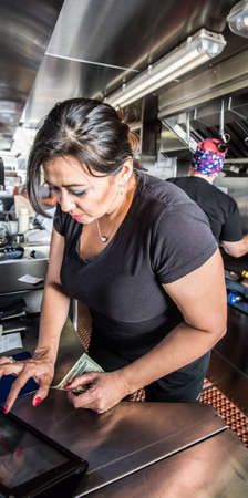 food service occupation: Female cashier with money on busy food truck