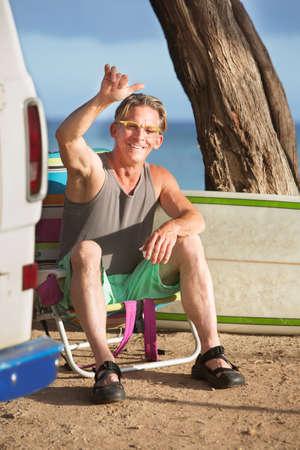 gesturing: Athletic single male surfer gesturing at ocean beach