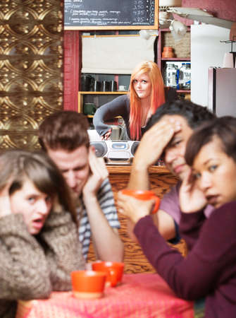 disrespectful: Young cafe employee trying to kick out customers with loud music Stock Photo