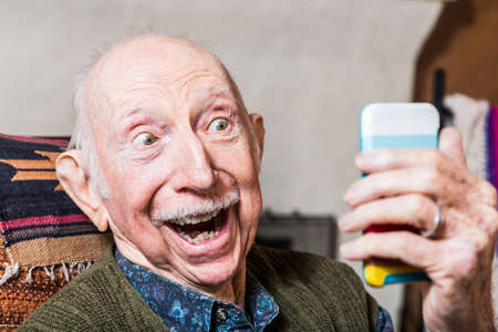 adulto mayor feliz: Caballero mayor que toma una selfie con smartphone