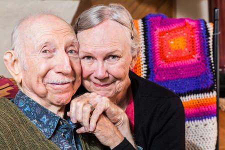 Glücklich älteres Ehepaar sitzt im Wohnzimmer mit Gesichtern zusammen