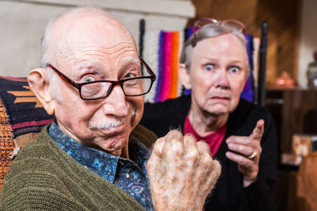 Tough elderly couple indoors with aggressive gesturing