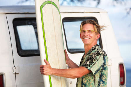 wind blowing: Handsome man with surfboard and wind blowing his hair