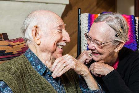 Caucásica feliz pareja de ancianos sentados adentro sonriente Foto de archivo