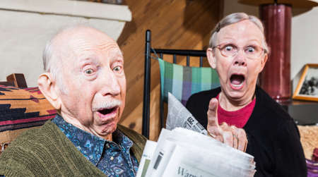 Angry older couple reading newspaper in living-room