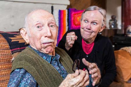 personas discutiendo: Argumentando mujer mayor con el puño cerrado y el marido confundido