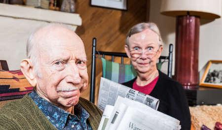 grumpy: Cute elderly husband and wife reading newspapers