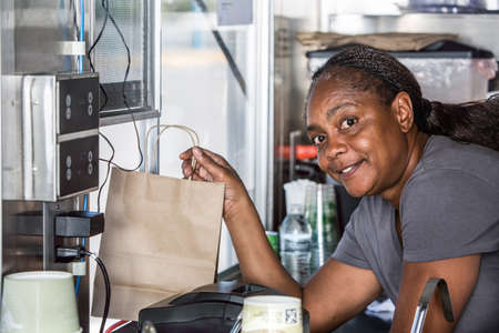 Smiling African-American worker hands order out window of modern food truck