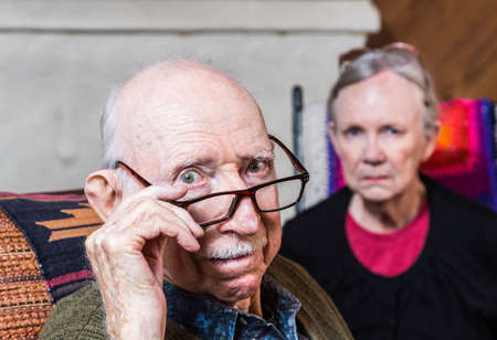 Concerned elderly couple sitting in livingroom scowling