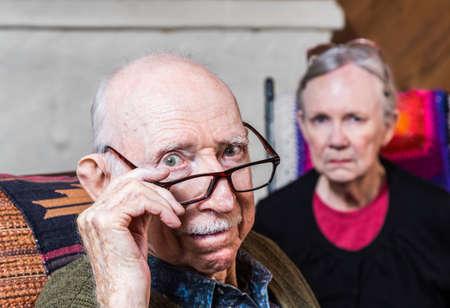 Concerned elderly couple sitting in livingroom scowling