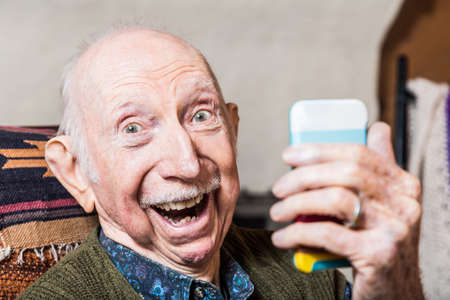 old technology: Older gentleman taking a selfie with smartphone