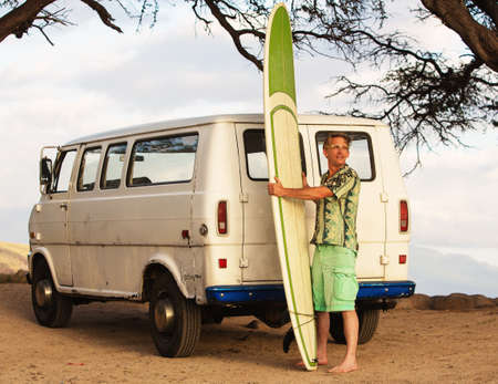 male surfer: Grinning male surfer with surfboard and van on beach Stock Photo