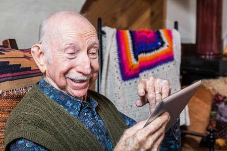 Smiling older gentleman working on a tablet in his living-room