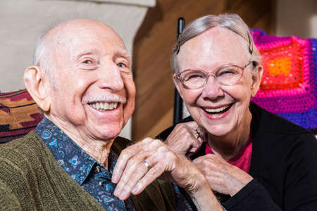 Happy older couple sitting in living-room smiling at camera