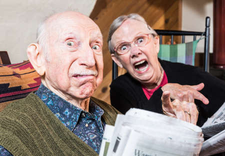 glower: Old mad couple reading a newspaper in their living-room