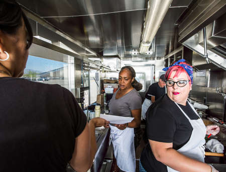 Female chef with pink hair works alongside crew on food truck