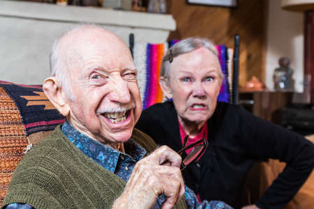 Angry old couple sitting indoors with scowling expression