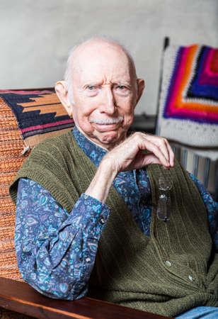 cynical: Stern elder gentleman sitting on chair in livingroom
