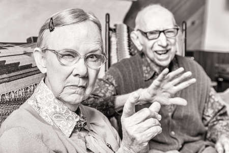 Toned image of angry old couple sitting in living room woman pointing Stock Photo - 43763040