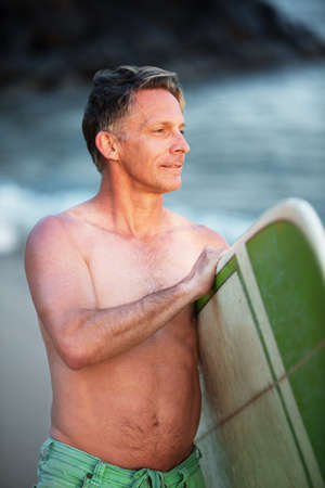 looking over: Confident middle aged surfer with surfboard looking over